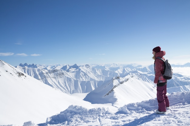 Standing young woman with backpack on the mountain peak against beautiful mountains and glacier Premium Photo