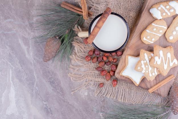 シナモンと牛乳のカップと木の板上の星と卵形のジンジャーブレッドクッキー 無料写真