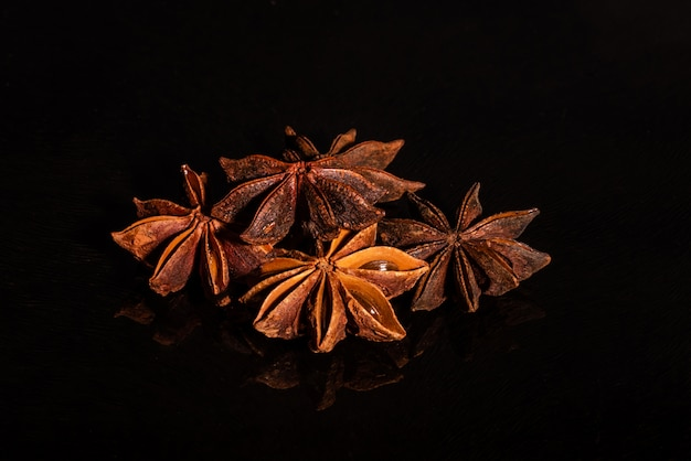 Star anise against a dark background. spice on a glass background with reflection Premium Photo