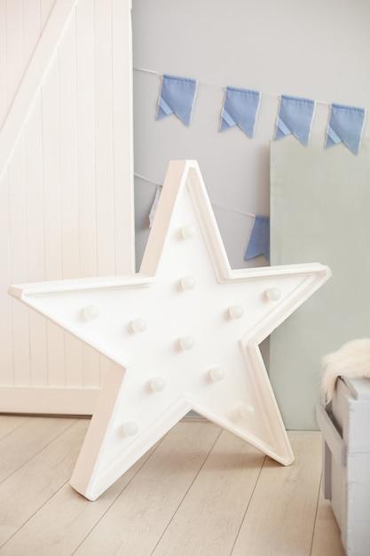 Звездная лампа на полу серой стены с праздничными флагами. большая звезда с лампочками. современные предметы интерьера. декоративная звезда с лампами. звездообразные белые светодиодные фонари с одиночной рамой Premium Фотографии