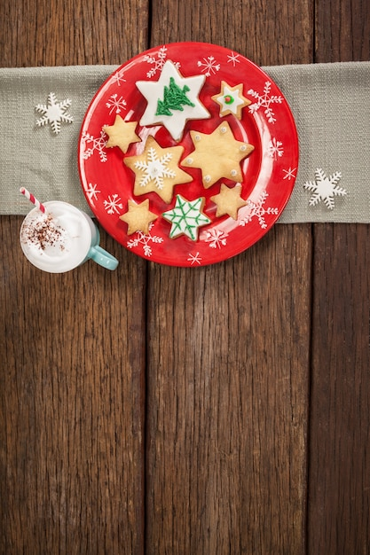 Star shaped cookies on a red plate and cup with cream Free Photo