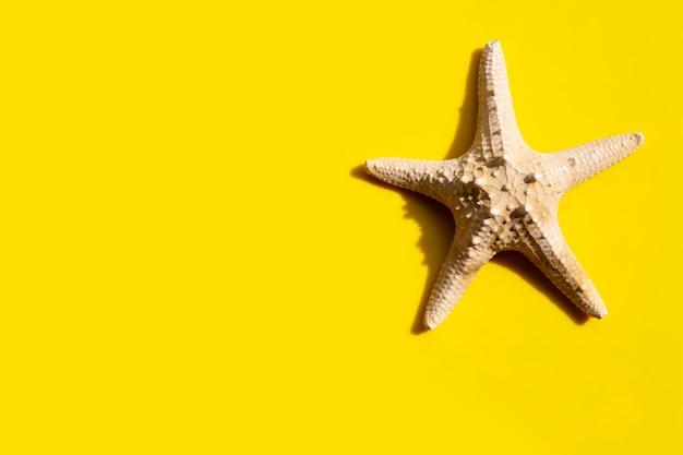 Морская звезда на желтом. наслаждайтесь концепцией летнего отдыха. Premium Фотографии