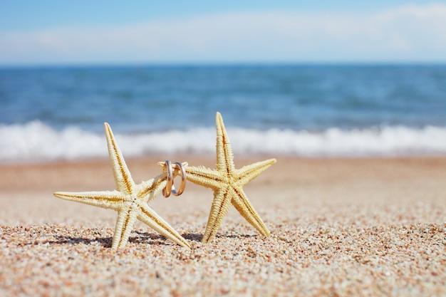 ビーチで結婚指輪とヒトデ Premium写真