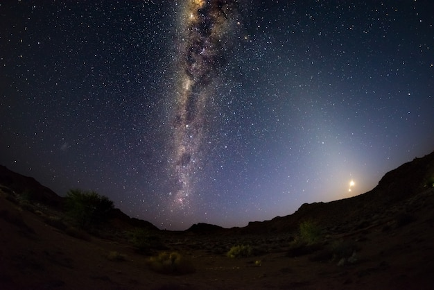 Starry sky and milky way arch with rising moon, captured from the namib desert in namibia, africa. Premium Photo