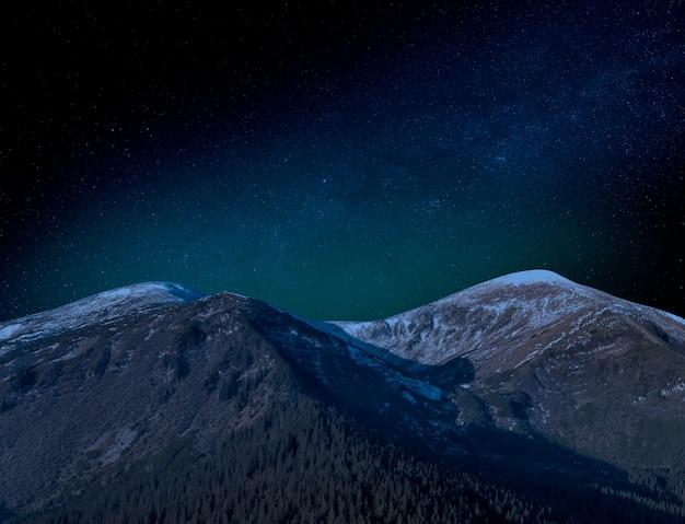 부분적으로 눈 덮인 산 꼭대기에 별이 빛나는 하늘. 그림 같은 밤 풍경. 프리미엄 사진