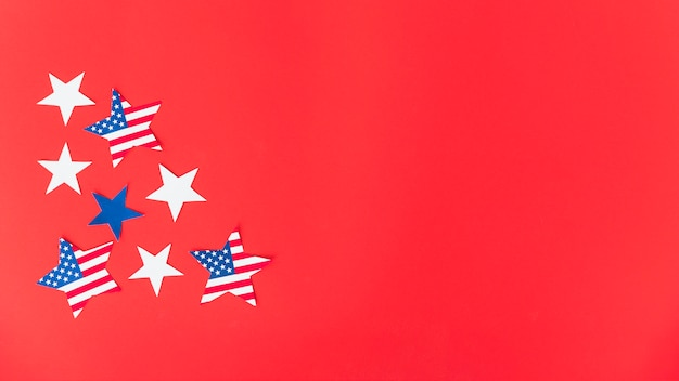 Stars in american flag color on red surface Free Photo