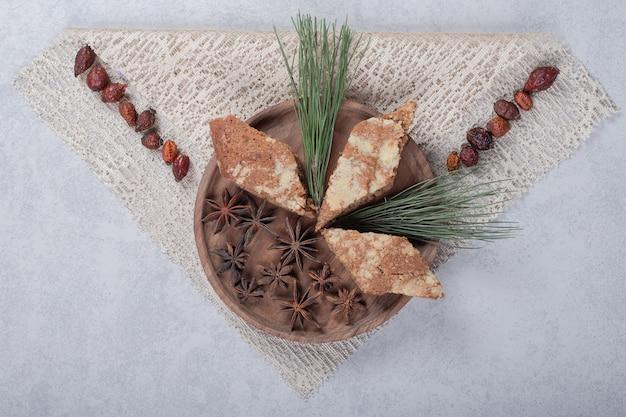 星は木の板に3つの甘いパイでアニスします。 無料写真