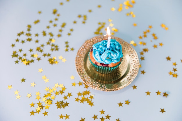 Stars spread around the illuminated candle over the cupcake on golden plate Free Photo