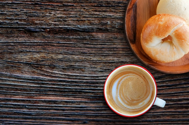 Start the day by fresh homemade bagel bread and hot coffee latte Premium Photo