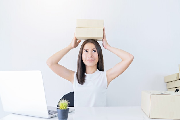 Start up small business entrepreneur sme or freelance woman holding boxes working at home concept Premium Photo