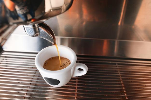Inizia la giornata con una tazza di bevanda aromatica. elegante macchina per caffè espresso nero che prepara caffè, girato nella caffetteria. Foto Gratuite