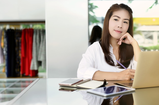 Starting new business. beautiful asian woman using digital tablet and laptop with smile while sitting at the clothing store. Premium Photo