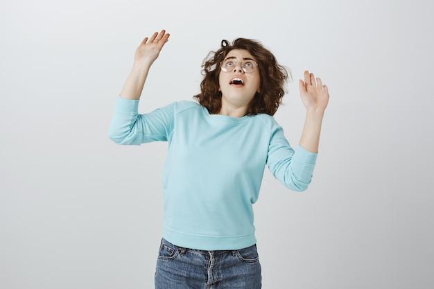 깜짝 놀란 소녀는 손을 들고 무언가가 그녀에게 떨어지는 것처럼 응시합니다. 무료 사진