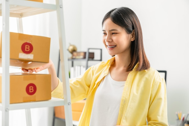 Startup small business, young asian woman checking and packing boxes for products to send to customers. working at the home office. Premium Photo