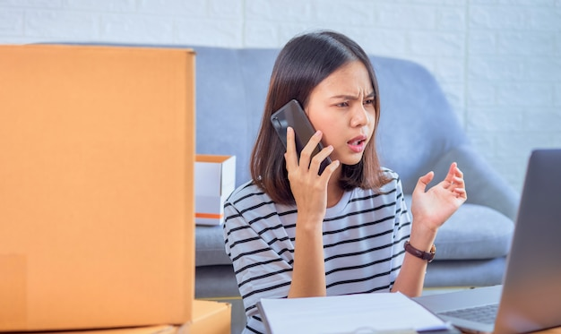 Startup small business , young asian woman owner talking on the smartphone with customers about ordering products, seller prepares the delivery box. Premium Photo
