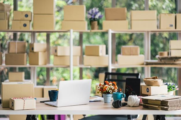 Интерьер домашнего офиса startup с коробкой посылок на полках, ноутбуком, кофейной чашкой и сканером штрих-кода на столе, рабочей областью Premium Фотографии