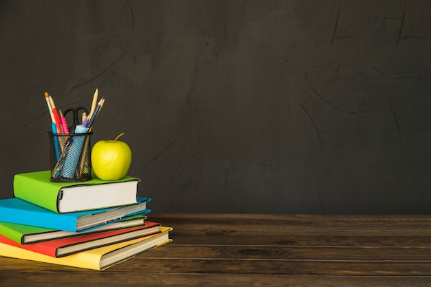 Stationary and apple on pile of books at table Free Photo