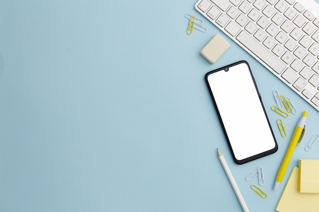 Stationary arrangement on blue background with phone and copy space Premium Photo