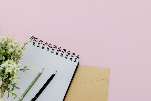 Stationary concept,  pencil, pen  and notepad  on a pink abstract table with copy space, minimal Premium Photo