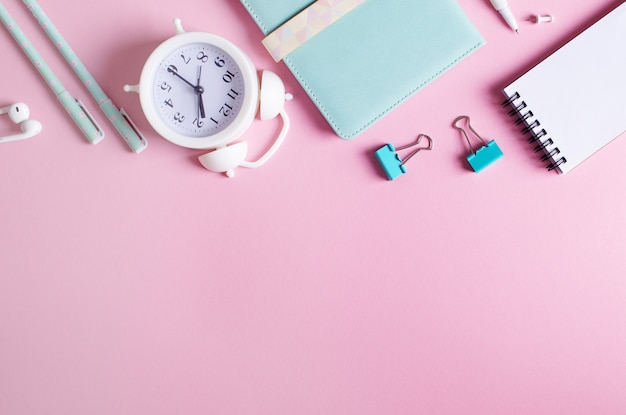 Stationary concept, top view flat lay photo of pencils, paper clips, alarm clock, notepads, in white and blue on pink background with copy space. Premium Photo