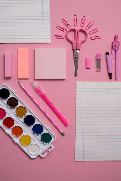Stationary , flat lay top view photo of scissors, pencils, paper clips,calculator,sticky note,stapler and notepad in pink and blue tone on pink background with copyspace. Premium Photo
