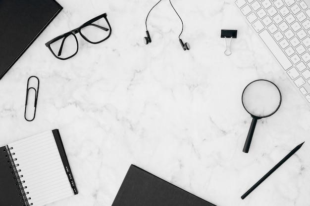 Stationeries; keyboard and eyeglasses on white marble textured background Free Photo