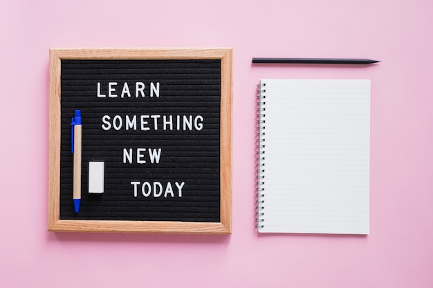 Stationeries with learn something new today text on slate over pink backdrop Free Photo