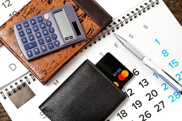 Канцелярские товары и кошелек с кредитными картами на деревянном Premium Фотографии