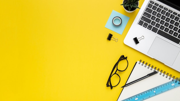 Stationery arrangement on yellow background with copy space Premium Photo