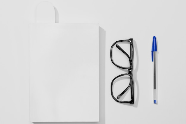 Stationery book and pen with reading glasses Free Photo