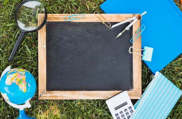 Stationery and chalk board set on green lawn Free Photo