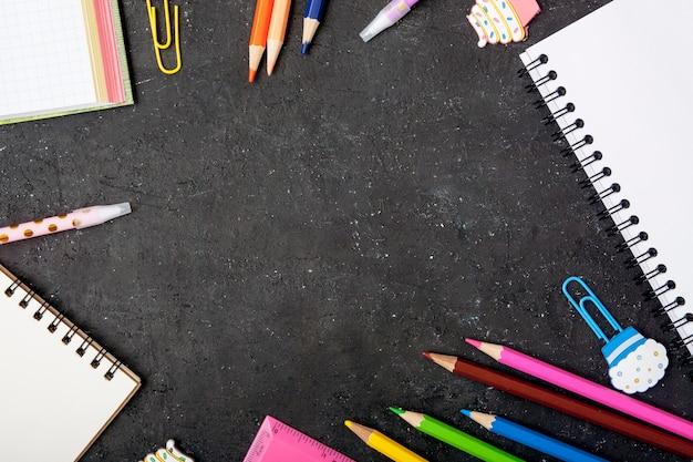 文房具は黒い背景にフレームを形成しました。コピースペースと学校のコンセプトに戻る Premium写真