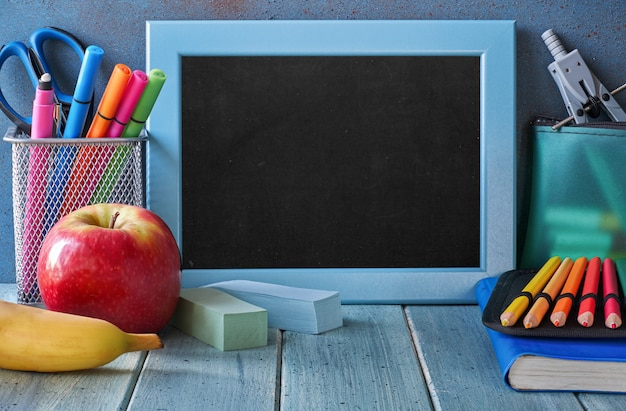 Stationery and fruits on a table in front of blackboard with text space Premium Photo
