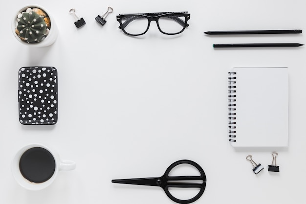 Stationery and glasses near case and coffee cup Free Photo