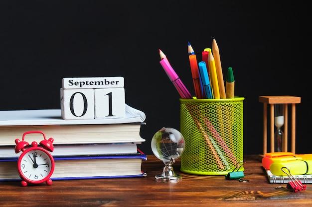 Канцелярские металлические стаканчики с карандашами рядом с книгами и сентябрьским календарем Premium Фотографии