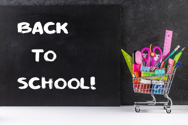 Stationery objects in mini supermarket cart on chalkboard background Premium Photo