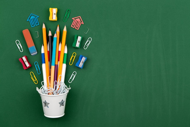 Stationery pencils paper clip pen eraser in a white bucket. still life on green school board background. copy space flat lay top view concept education Premium Photo