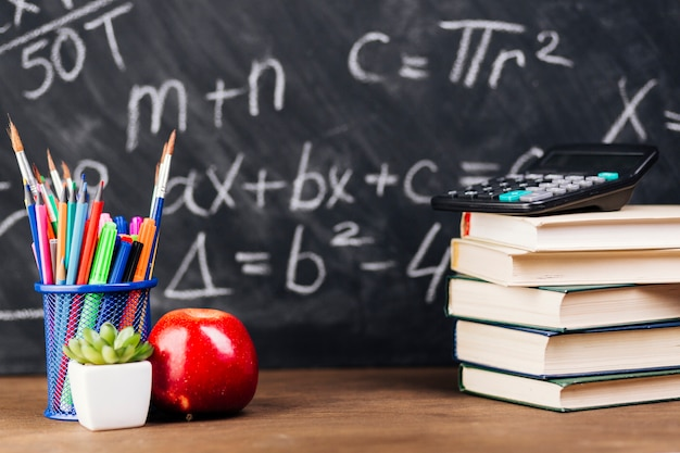 Stationery and stacked books placed on desk on chalkboard background Free Photo