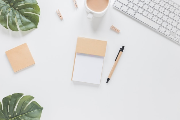 Stationery on white table with green leaves and keyboard Premium Photo