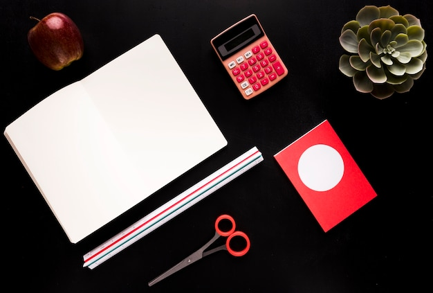 Stationery with fruit on black table Free Photo