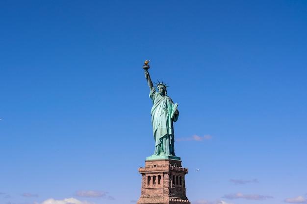 The statue of liberty under the blue sky background, lower manhattan, new york city Premium Photo