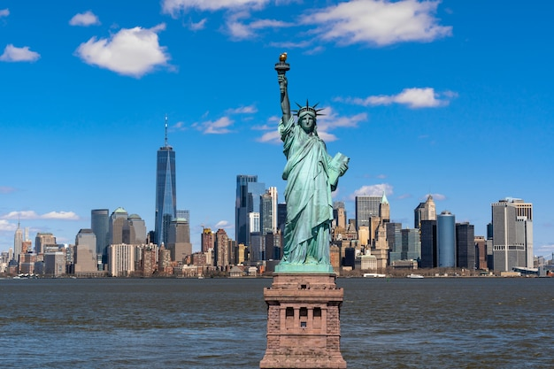 The statue of liberty over scene of new york cityscape river side which location is lower manhattan Premium Photo