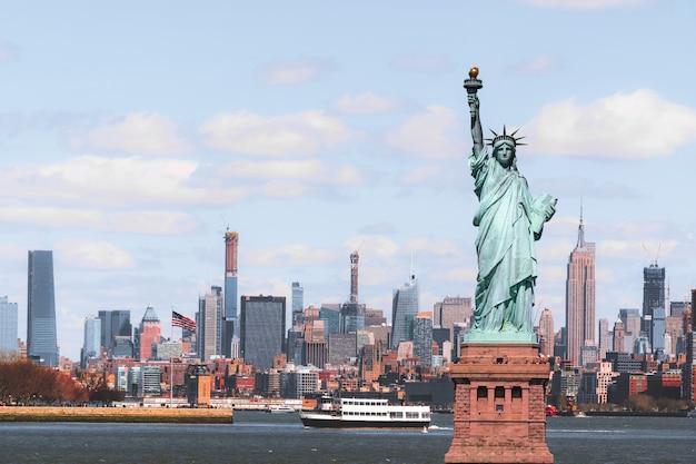 The statue of liberty over the scene of new york cityscape river side Premium Photo