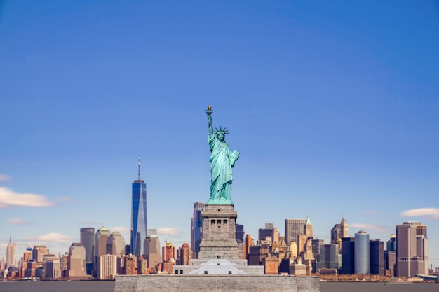 The statue of liberty with the one world trade building center over hudson river and new york cityscape background, landmarks of lower manhattan new york city. Premium Photo