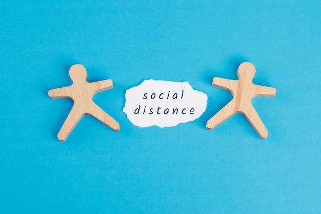 Оставайтесь дома концепции с социальной расстояние текста на рваной бумаги, деревянные фигуры на синем столе плоской планировки. Бесплатные Фотографии