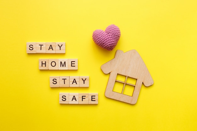 Stay home text with wooden house with knitted heart on yellow background. quarantine concept, covid-19 virus protection. top view, flat lay. Premium Photo
