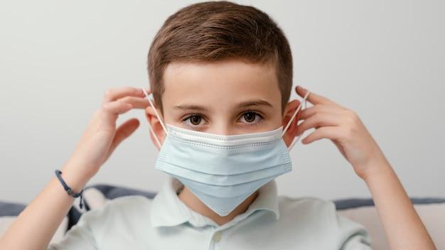 医療用マスクを着用して屋内にいる子供 無料写真