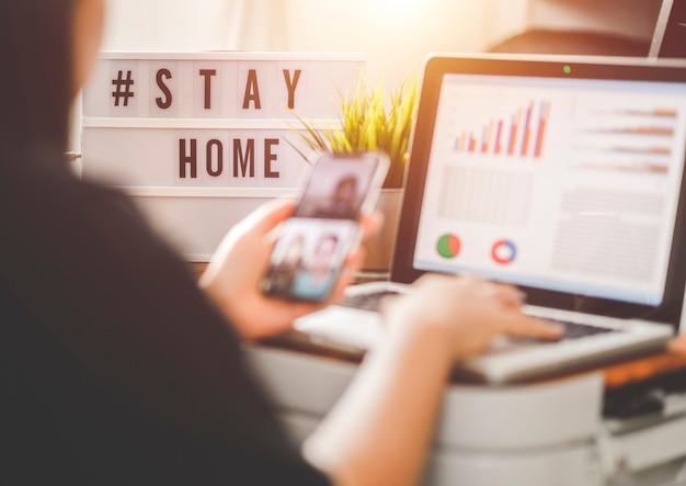 Лайтбокс с текстовым хэштегом #stayhome, светящимся в свете и размытой женщиной, работающей дома. офисный работник на карантине. работа на дому, чтобы избежать вирусных заболеваний. концепция фрилансера или удаленного работника. Premium Фотографии