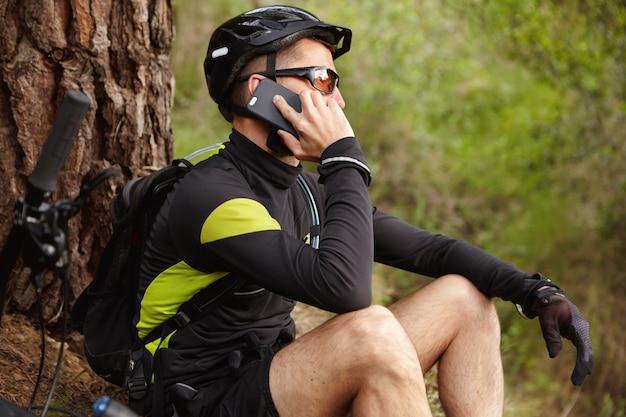 接続を維持します。ヘルメットと携帯電話で話している眼鏡を身に着けているハンサムな若いヨーロッパのバイカーのショットをトリミング 無料写真