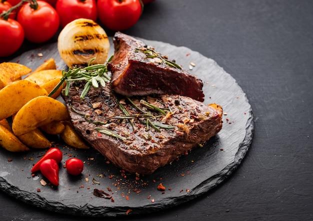 Стейк из говядины. стейк из говядины среднего размера с красным перцем, ароматными травами и жареным луком Premium Фотографии